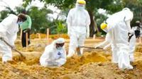 Proses pemakaman jenazah Dovid-29 di Riau oleh tukang gali kubur. (Liputan6.com/M Syukur)