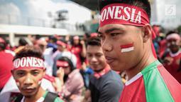 Suporter Garuda Muda mengecat pipinya dengan gambar bendera Merah Putih untuk mendukung Timnas Indonesia U-22 pada laga melawan Timor Leste, Minggu (20/8). Indonesia melakoni laga ketiga dalam lanjutan grup B SEA Games 2017. (Liputan6.com/Faizal Fanani)