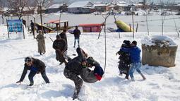 Sejumlah pria bermain di lapangan yang tertutup salju di Srinagar, kawasan Kashmir yang dikuasai India, Sabtu (5/1). Wilayah Kashmir mengalami salju selama beberapa hari yang mengakibatkan terputus jalan raya Jammu-Srinagar (AP Photo/Dar Yasin)