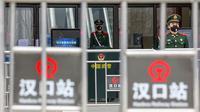Polisi paramiliter berjaga di luar Stasiun Kereta Api Hankou yang ditutup di Wuhan, Provinsi Hubei, China, Kamis (23/1/2020). Pemerintah China mengisolasi Kota Wuhan yang berpenduduk sekitar 11 juta jiwa untuk menahan penyebaran virus corona. (Chinatopix via AP, File)