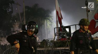 Bendera Merah Putih terbalik akibat kericuhan antara massa aksi dengan personil kepolisian yang berusaha menghalau massa yang berlaku anarkis di sekitar Gedung Bawaslu, Jalan MH Thamrin, Jakarta, Rabu (22/5/2019). Aksi unjuk rasa yang dimotori GNKR berakhir ricuh. (Liputan6.com/Helmi Fithriansyah)