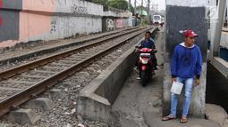 Pengendara melintas di samping kereta yang tengah melintas di kawasan Banjir Kanal Barat, Jakarta, Selasa (20/3). Selain mempersingkat waktu, pengendara beralasan hal itu demi memperpendek jarak tempuh. (Liputan6.com/Arya Manggala)
