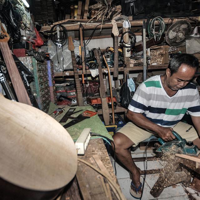Potret Bone di sela aktivitasnya di workshop Bone's Costum Guitar, Jatinegara, Jakarta, Rabu (10/3/2021). Bone berharap Covid-19 segera hilang agar usahanya dapat kembali bangkit dan menciptakan produk gitar dalam negeri yang membanggakan. (merdeka.com/Iqbal S Nugroho)