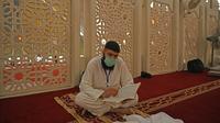 Pria Muslim dengan mengenakan masker saat membaca Alquran saat beritikaf di Masjid Agung Faisal di Islamabad, Pakistan, Kamis (14/5/2020). Itikaf adalah berdiam diri di masjid dengan niat beribadah untuk mendekatkan diri kepada Allah swt pada sepuluh hari terakhir bulan Ramadan. (Aamir QURESHI/AFP)