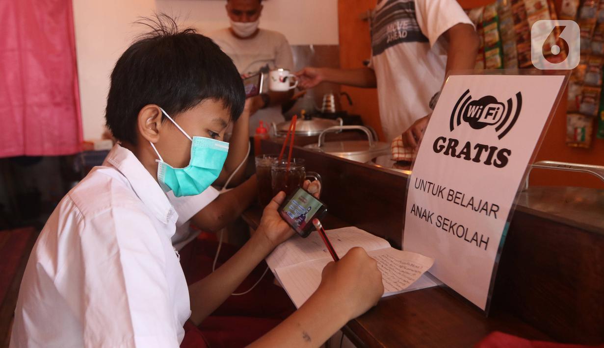 Seorang siswa sekolah dasar belajar dengan menggunakan wifi gratis yang disediakan oleh warkop Rizki, di Pondok Aren, Tangerang Selatan, Rabu (29/7/2020). Warung kopi tersebut menyediakan wifi gratis dan peminjaman laptop serta handphone. (Liputan6.com/Angga Yuniar)