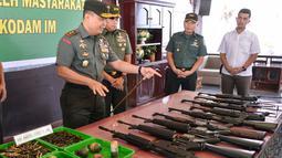 Panglima Kodam Iskandar Muda Mayjen TNI Teguh Arief Indratmoko memeriksa senjata bekas konflik di Banda Aceh, Aceh, Rabu (15/5/2019). Sembilan senjata laras panjang, tiga pistol, delapan granat, dan 455 butir amunisi tersebut diserahkan secara sukarela oleh warga. (CHAIDEER MAHYUDDIN/AFP)