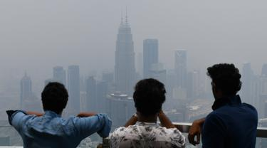 "Wisatawan melihat cakrawala Kuala Lumpur, termasuk Menara Kembar Petronas, yang diselimuti kabut asap di Kuala Lumpur (11/9/2019). Kualitas udara turun ke tingkat ""tidak sehat"" di  sekitar Kuala Lumpur, menurut indeks polusi udara pemerintah. (AFP Photo/Mohd Rasfan)"