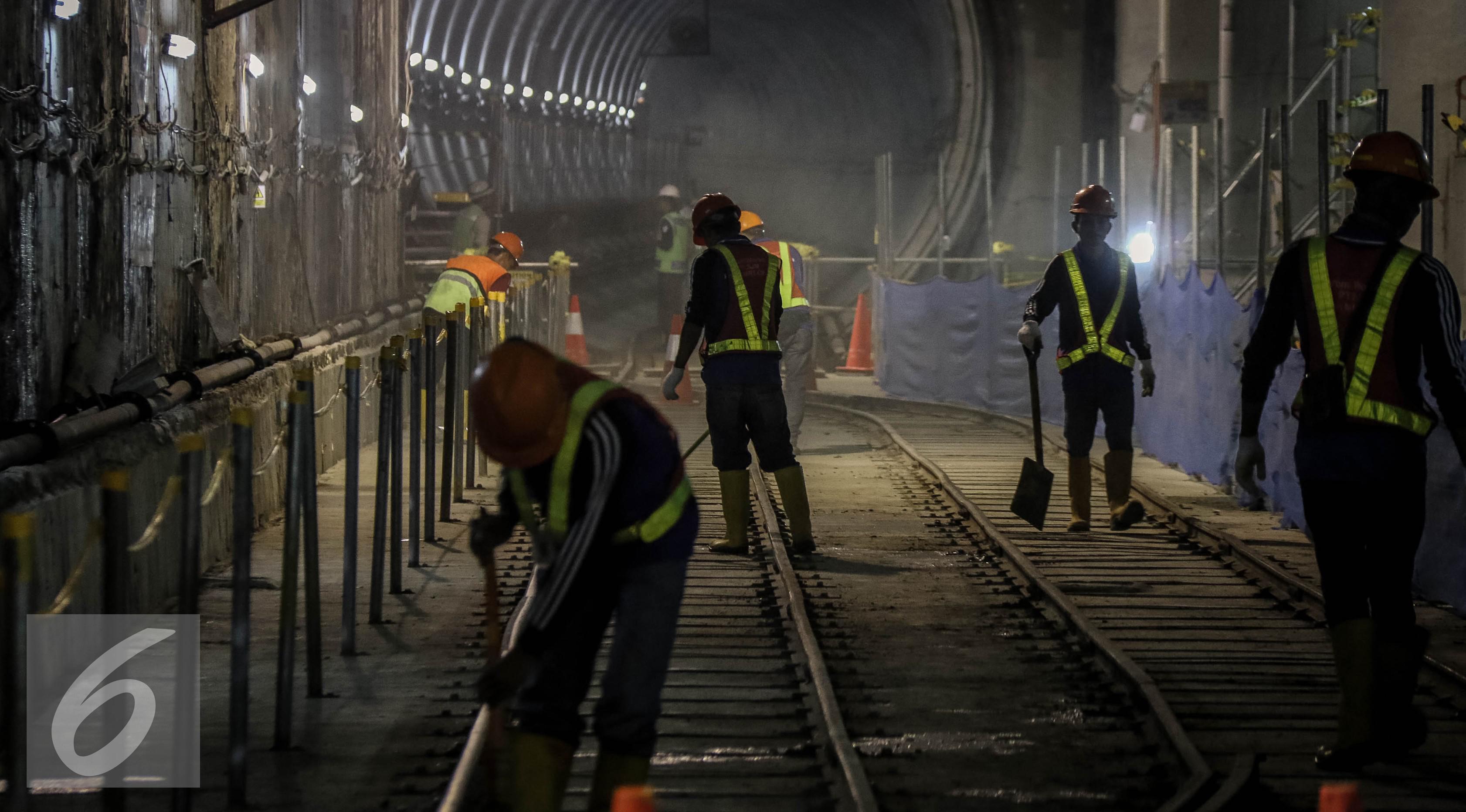 Para pekerja membersihkan jalur rel di terowongan Mass Rapid Transit (MRT) di Dukuh Atas, Jakarta, Jumat (30/9). Jumlah stasiun yang dilalui di rute tersebut sebanyak 13 stasiun. (Liputan6.com/Faizal Fanani)