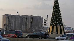 Kendaraan melintas di samping pohon Natal dengan daftar nama korban yang tewas dalam insiden ledakan di Pelabuhan Beirut terlihat di dekat silo gandum yang rusak di Beirut, Lebanon (22/12/2020). Ledakan juga menyebabkan 300.000 orang kehilangan tempat tinggal. (Xinhua/Bilal Jawich)