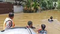 Sejumlah petugas menarik perahu karet saat proses evakuasi korban banjir di kawasan Pela Mampang Pulo, Jakarta, Kamis (2/1/2020). Sejumlah rumah di kawasan Pela Mampang Pulo terpantau masih terendam banjir. (Liputan6.com/Herman Zakharia)