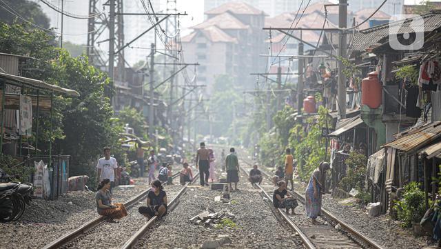 Aktivitas warga berjemur di bantaran rel di kawasan pemukiman padat Pejompongan, Jakarta, Selasa (6/7/2021). Berjemur diri di bawah matahari di antara pukul 08.00-11.00 WIB merupakan salah satu upaya paling sederhana untuk menjaga kesehatan selama wabah virus COVID-19. (Liputan6.com/Faizal Fanani)