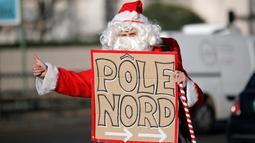 Seorang petualang asal Prancis, Remi Le Calvez membawa poster bertuliskan 'Pole Nord' yang artinya kutub utara, mencari tumpangan kendaraan dengan mengenakan kostum Santa Claus di Paris, Prancis, Selasa (6/12). (Reuters/Benoit Tessier)