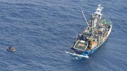 Kapal nelayan menyelamatkan perahu pengangkut tujuh penumpang selamat kapal feri MV Butiraoi yang hilang di perairan Pasifik di Kiribati, Minggu (28/1). Mereka berhasil bertahan hidup tanpa air maupun peralatan komunikasi. (New Zealand Defence Force/AP)
