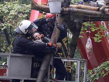 Polisi menyeret aktivis lingkungan dari sebuah rumah pohon di hutan Hambacher Forst di Kerpen, Jerman Barat (13/9). Aktivis yang tinggal di rumah pohon tersebut menghadapi penggusuran paksa oleh polisi. (Henning Kaiser/dpa/AFP)