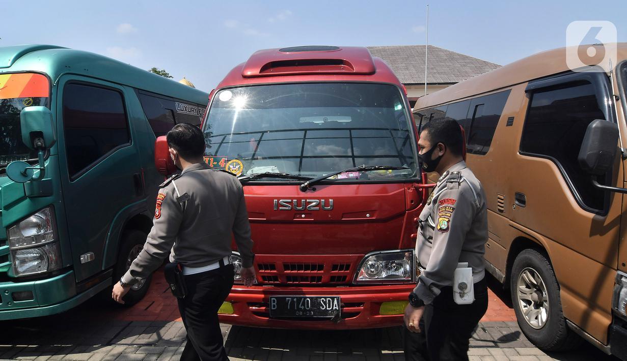 Petugas polisi memeriksa mobil travel gelap yang disita di halaman Polres Metro Kabupaten Bekasi, Jawa Barat, Senin (10/5/2021). Satlantas Polres Metro Bekasi mengamankan 32 travel gelap yang masih beroperasi saat larangan mudik dari tanggal 6-17 Mei 2021. (Liputan6.com/Herman Zakharia)
