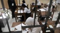 Siswa Sekolah Menengah Pertama Luar Biasa (SMPLB) Kategori B atau tunarungu saat mengerjakan Ujian Nasional Kertas Pensil (UNKP) di SLB Negeri 7 Jakarta, Selasa (24/4). UNKP di SLB tersebut diikuti oleh delapan peserta. (Merdeka.com/Iqbal Nugroho)