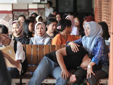 Orangtua murid menunggu antrean pengambilan nomor token PPDB DKI Jalur Zonasi di SMA Negeri 21, Jakarta, Senin (24/6/2019). Pendaftaran PPDB DKI Jakarta Jalur Zonasi SMP-SMA dibuka pada 24-26 Juni 2019 mulai pukul 08.00-16.00 WIB. (merdeka.com/Iqbal Nugroho)