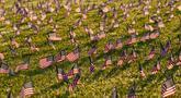 Aktivis dari COVID Memorial Project meletakkan ribuan bendera Amerika berukuran kecil di di halaman National Mall di Washington, Selasa (22/9/2020). Ribuan bendera itu menandai 200 ribu nyawa yang hilang akibat virus corona Covid-19 di Amerika Serikat. (AP Photo/J. Scott Applewhite)