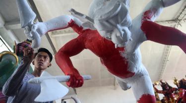 Seorang seniman mencat patung atau yang dikenal ogoh-ogoh sebelum Perayaan Nyepi di Denpasar, Bali (12/3). Perayaan Nyepi akan jatuh apada tanggal 17 Maret 2017. (AFP Photo/Sonny Tumbelaka)