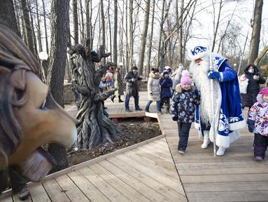 "Seorang staf yang mengenakan kostum karakter dongeng Rusia, Kakek Frost, berjalan bersama anak-anak dalam pembukaan ""Jalur Dongeng"" di ""Kediaman Kakek Frost"" di Moskow, Rusia (18/11/2020). . (Xinhua/Alexander Zemlianichenko Jr)"