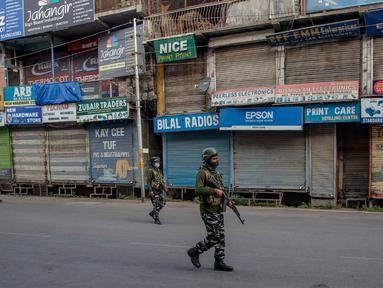 Paramiliter bersenjata melakukan patroli di jalan yang dikosongkan di Srinagar, Kashmir yang dikuasai India, Rabu (5/8/2020). Tentara India memperketat keamanan di Kashmir dalam upaya menahan serangan dalam peringatan setahun pelepasan status otonomi khusus wilayah tersebut. (AP Photo/ Dar Yasin)