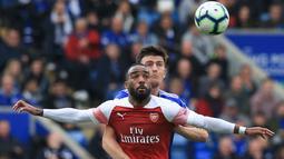 Bek Leicester City, Harry Maguire berebut bola dengan penyerang Arsenal, Alexandre Lacazette pada pertandingan Liga Inggris di King Power Stadium pada 28 April 2019. Harry Maguire pun kini berstatus bek termahal dunia. (AFP Photo/Lindsey Parnaby)