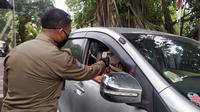 Petugas Satpol PP Kota Bogor sedang memeriksa suhu tubuh tamu yang hendak masuk ke kawasan Balai Kota Bogor, Rabu (10/6/2020). (Liputan6.com/Achmad Sudarno)