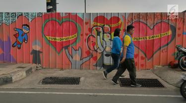 Pejalan kaki melintasi mural yang menghiasi tembok di kawasan Margonda, Depok, Sabtu (16/2). Gambar mural memiliki pesan agar masyarakat tetap damai dan berteman meski berbeda dalam memilih calon presiden dalam Pilpres 2019. (Liputan6.com/Herman Zakharia)
