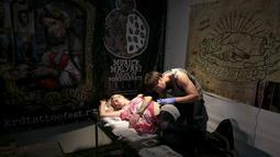 Seorang wanita terbaring saat di tato oleh seniman selama acara Festival Tato Internasional di Sochi, Rusia, (23/4). Sejumlah wanita tampak antusias untuk mentato tubuhnya di festival tato terbesar di negara tersebut. (REUTERS/Kazbek Basayev)