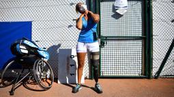 Atlet para tenis Prancis Pauline Deroulede melakukan strech sebelum pertandingan selama edisi ke-4 turnamen tenis kursi roda French Riviera Open di Biot, 28 September 2020. Pauline Deroulede saat ini tengah fokus terhadap Paralimpiade Paris 2024. (Photo by FRANCK FIFE/AFP)