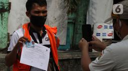 Petugas Satpol PP (kanan) memotret warga pelanggar PSBB yang terjaring razia masker di Jalan Tanjung Duren Raya, Jakarta, Jumat (11/9/2020). Petugas Satpol PP gencar melakukan razia masker menyusul kasus COVID-19 di DKI Jakarta yang terus meningkat. (merdeka.com/Imam Buhori)