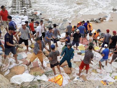 Personel militer dan warga bekerja sama memperkuat tanggul pemecah ombak di Provinsi Thua Thien-Hue, Vietnam, 20 Oktober 2020. Bencana alam menyebabkan 105 orang tewas dan 27 lainnya hilang di sejumlah wilayah tengah dan dataran tinggi tengah Vietnam sejak awal Oktober. (Xinhua/VNA)