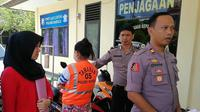 Seorang bidan berinisial RK (32) ditangkap anggota Polsek Baruga Kota Kendari lantaran terjerat berbagai kasus penipuan. (Liputan6.com/ Ahmad Akbar Fua)