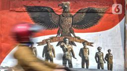 Pengendara melintas di depan mural bertemakan Pancasila di Kampung Pancasila kawasan Galur, Johar Baru, Jakarta, Selasa (1/6/2021). Mural di Kampung Pancasila ini juga untuk mempercantik lingkungan.tersebut. (merdeka.com/Iqbal S. Nugroho)