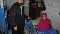 Corfied (Kiri) dan Iyah Lasmini (Kanan) serah terima bantuan kursi roda dari Disabilitas Tanpa Batas. Foto: Dokumen DTB.