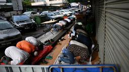 Sejumlah umat muslim Malaysia melakukan salat Idul Fitri di depan toko yang berada di sekitar Masjid India di Kuala Lumpur, Malaysia (25/6). (AFP Photo/Manan Vatsyayana)