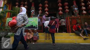 Seorang warga membawa sembako yang di bagikan oleh warga keturunan Tionghoa di Klenteng Fuk Ling Miau, Yogyakarta, Jumat (1/7). Pembagian sembako dilakukan sebagai bentuk kepedulian terhadap sesama di bulan ramadan. (Liputan6.com/Boy Harjanto)