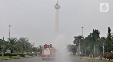 Petugas pemadam kebarakan menyemprotkan cairan disinfektan di kompleks Monumen Nasional (Monas), Jakarta, Senin (30/3/2020). Penyemprotan disinfektan ini dilakukan guna memutus rantai penyebaran virus Corona atau Covid-19 di pusat kota. (merdeka.com/Iqbal S. Nugroho)
