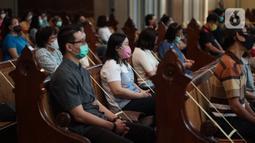 Jemaat duduk di antara pembatas jarak tubuh saat melaksanakan ibadah misa di Gereja Katedral Jakarta, Minggu (12/7/2020). Gereja Katedral Jakarta kembali menggelar misa bagi umat Katolik dengan menerapkan protokol kesehatan untuk mencegah penularan Covid-19. (Liputan6.com/Immanuel Antonius)