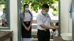 Para siswa yang mengenakan masker mengantre untuk mencuci tangan di sebuah sekolah di Vientiane, Laos, Selasa (19/5/2020). Siswa tingkat akhir sekolah dasar, menengah pertama, dan menengah di Laos sudah mulai bersekolah sejak 18 Mei 2020. (Xinhua/Kaikeo Saiyasane)