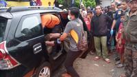 Sejumlah petugas identifikasi Polres Tasikmalaya tengah mengeluarkan mayat seorang Kepala Sekolah Sekolah Dasar di Tasikmalaya, Jawa Barat yang meninggal di dalam mobilnya (Liputan6.com/Jayadi Supriyadin)