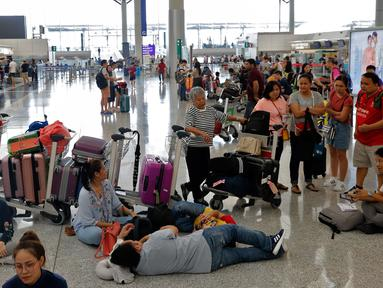 Calon penumpang menunggu jadwal keberangkatan pesawat di bandara Hong Kong, Rabu (14/8/2019). Bandara Hong Kong kembali membuka penerbangan keberangkatan pada Rabu pagi setelah sempat lumpuh selama dua hari akibat demonstran menduduki salah satu bandara tersibuk di dunia tersebut. (AP/Vincent Thian)
