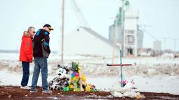 Orang-orang memberi penghormatan di lokasi kecelakaan bus di Provinsi Saskatchewan, Kanada (9/4). Sebelumnya sebuah bus yang membawa tim hoki Humboldt Broncos junior menabrak truk dan menewaskan 14 orang. (Jonathan Hayward/The Canadian Press via AP)