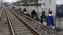 Sejumlah pengendara melintas di samping rel kereta yang berada di kawasan Banjir Kanal Barat, Jakarta, Selasa (20/3). Aksi nekat tersebut membahayakan diri sendiri maupun pengguna jalan lain. (Liputan6.com/Arya Manggala)