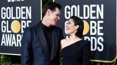 Komedian Jim Carrey dan Ginger Gonzaga bertatapan di karpet Golden Globe Awards ke-76 di Beverly Hills, California (6/1). Jim Carrey datang ke Golden Globes 2019 dengan menggandeng kekasih barunya, Ginger Gonzaga. (Frazer Harrison/Getty Images/AFP)