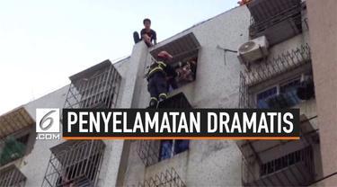 Bayi berumur 3 tahun tersangkut di jendela gedung lantai 7. bayi tersebut lolos dari maut setelah petugas pemadam kebakaran berhasil menyelamatkannya.