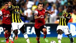 Duel perebutan bola antara Jack Wilshere dengan Joseph Yobo pada pertandingan Play-off Liga Champions antara Fenerbahce melawan Arsenal di Stadion Sukru Saracoglu di Istanbul pada 21 Agustus 2013. (AFP/Bulent Kilic)