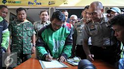 Perwakilan pengemudi ojek menandatangani deklarasi damai komunitas ojek pangkalan dengan komunitas ojek online di Polsek Kebun Jeruk, Jakarta (22/9/2015). Acara diselenggarakan unutk menjalin silaturahmi antar pengemudi ojek. (Liputan6.com/Gempur M Surya)