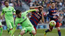 Gelandang Barcelona, Arda Turan, berebut  bola dengan gelandang Getafe, Alvaro Medran. Sementara bagi Getafe kekalahan ini membuat mereka terpuruk ke posisi 17, setinggat di atas zona degragasi. (Reuters/Albert Gea)