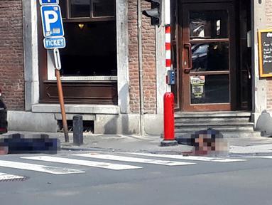 Seorang petugas polisi berdiri di lokasi dekat dua jenazah polisi korban penembakan di Liege, Belgia (29/5). Seorang pria menembak mati tiga orang di dekat sebuah kafe di Kota Liege, Belgia, Selasa waktu setempat. Dua di antara korban adalah polisi. (AP)